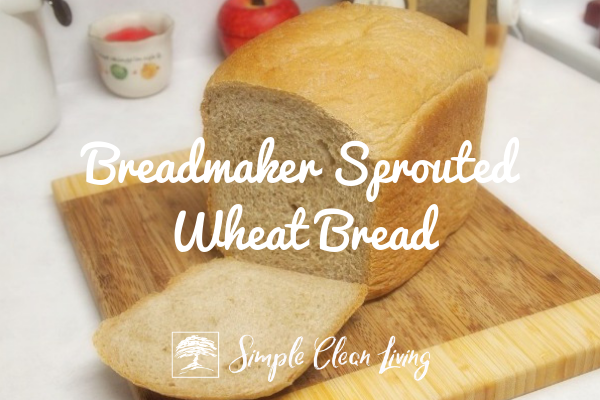 "A picture of a loaf of sliced bread on a cutting board and the blog post title ""Breadmaker Sprouted Wheat Bread"""