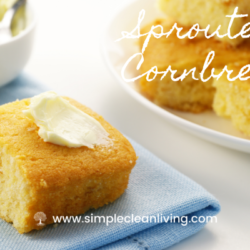 A plate piled with sprouted cornbread alongside a napkin with a piece of cornbread topped with butter