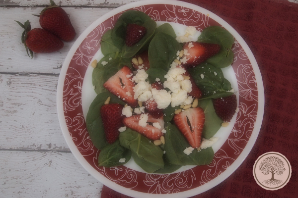 A plate with spinach and strawberry salad
