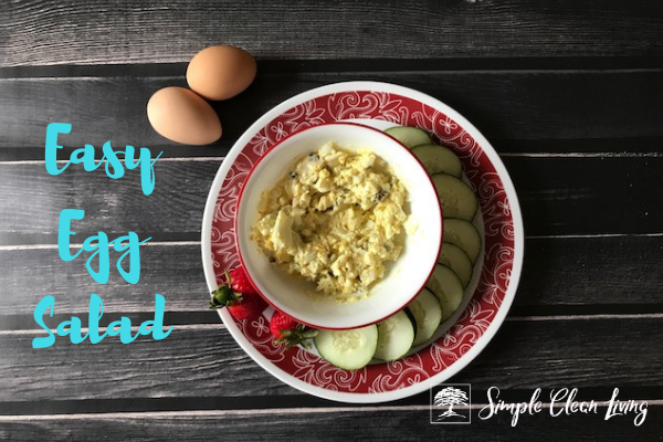 "A picture of a bowl of egg salad on a plate with cucumbers and strawberries and the blog post title ""Easy Egg Salad"""