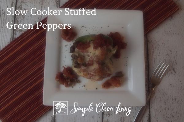 "A picture of a stuffed green pepper on a plate with the blog post title ""Slow Cooker Stuffed Green Peppers"""