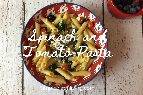 bowl of spinach and tomato pasta with the blog post title